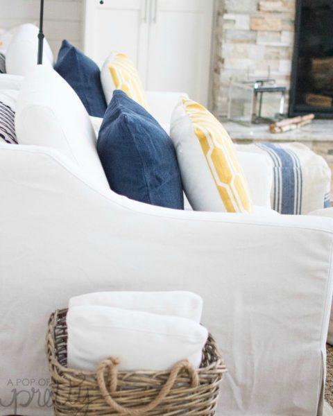 Coastal style lake house living room with blue striped poufs